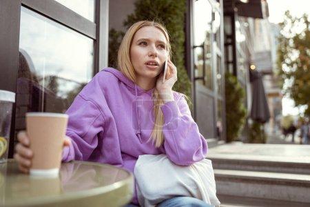 Foto de Esperándole. Niña concentrada que pasa el café en la cafetería y espera a su colega. - Imagen libre de derechos