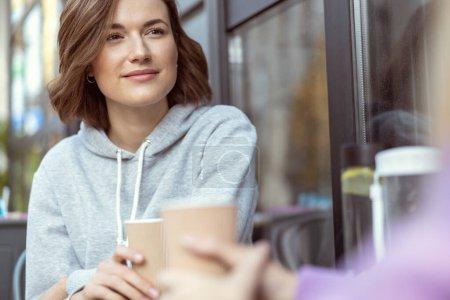 Foto de Una joven y soñada que disfruta de una reunión amistosa mientras escucha a su pareja. - Imagen libre de derechos
