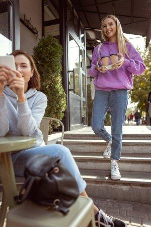 Foto de Seguirnos. Hermosa rubia demostrando su sonrisa, sosteniendo dos tazas de papel con café. - Imagen libre de derechos