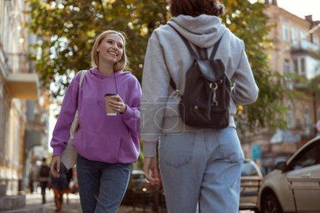 Foto de Chica alegre disfrutando de su café mientras pasea por la ciudad. - Imagen libre de derechos