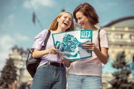 Foto de Sean serios. Una chica linda con mapa de la ciudad en ambas manos y escuchando a su amiga. - Imagen libre de derechos