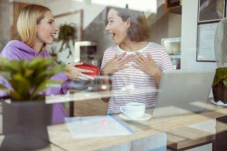 Foto de Sufrido. Muchacha agradable que celebra presentes en ambas manos mientras disfruta de un estado de ánimo festivo después de las clases. - Imagen libre de derechos