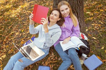Foto de Tiempo para prepararse. Joven chicas sentadas sobre el terreno y que completan sus tareas - Imagen libre de derechos