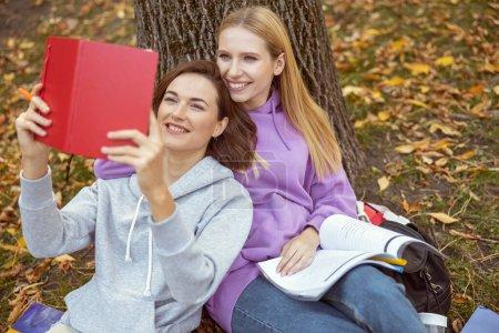 Foto de Queridas chicas que se apoyan en el árbol mientras se sientan en el suelo en el parque. - Imagen libre de derechos