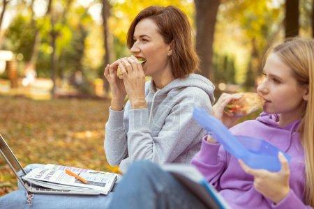 Foto de Estudiantes hambrientos que buscan una dirección mientras comen sus sándwiches. - Imagen libre de derechos