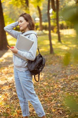 Foto de Una mujer feliz y positiva que tiene su portátil mientras va a visitar sus clases. - Imagen libre de derechos