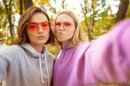 Foto de Únete a nosotros. Pequeñas mujeres vestidas de gafas elegantes mientras caminan por el parque - Imagen libre de derechos