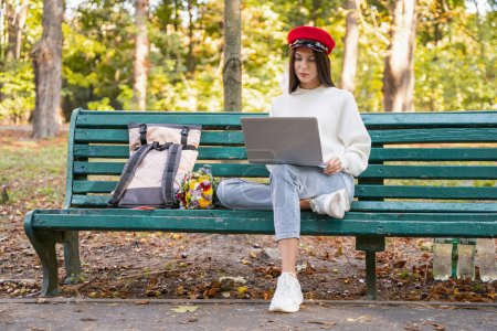 Photo for Relaxed atmosphere. Cute girl sitting on the bench and staring at screen of her laptop - Royalty Free Image