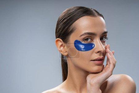Foto de Cuidado de belleza. Atractiva mujer joven aislada en gris y que mantiene parches oculares - Imagen libre de derechos
