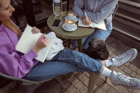 Photo for Coffee break. Attentive young female bowing head while making notes during conversation - Royalty Free Image