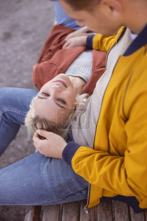 Photo for Good-looking young female closing her eyes lying on the lap of her man - Royalty Free Image