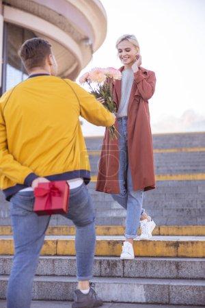Photo pour Homme debout dans les escaliers et donnant un bouquet de fleurs à une belle femme - image libre de droit