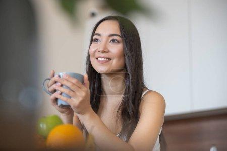 Photo pour Une jeune femme souriante se détendre à la maison avec une tasse de thé - image libre de droit
