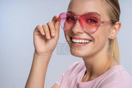 Photo pour Positive jolie dame dans des lunettes élégantes s'amuser à l'intérieur. Concept féminin de beauté et de détente - image libre de droit