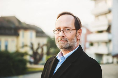 Photo pour Portrait extérieur d'un homme de 50 ans portant un manteau noir et des lunettes - image libre de droit
