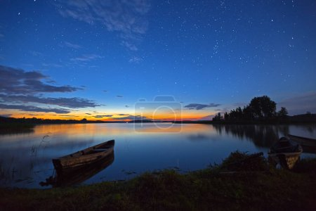 Stars Shining in sky at night over lake