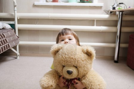 child hugging teddy bear, devotion concept, kid hiding behind the toy