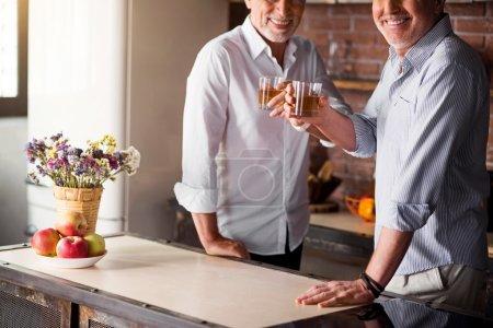 Two men rasing glasses in the kitchen