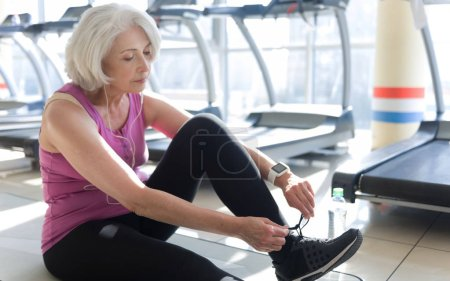 woman tying shoelaces in a gym.