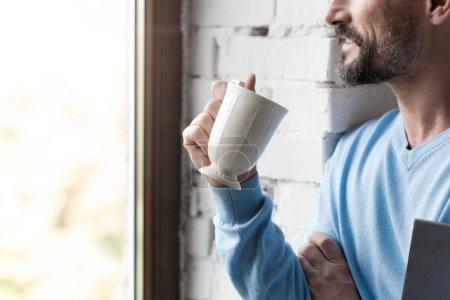 Pleasant joyful man drinking coffee