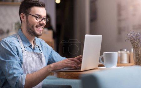 smiling happy man working on laptop.
