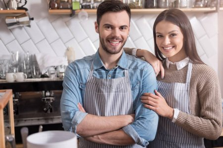 Smiling young couple hugging and standing behind the bar.