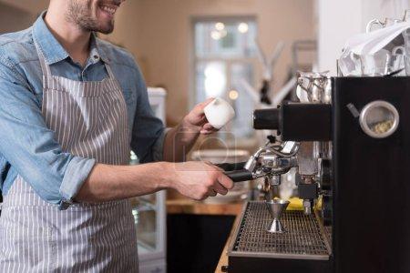 Pleasant smiling man using coffee machine.