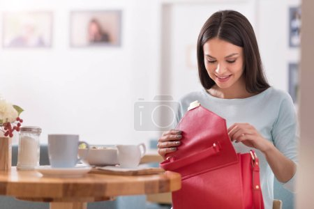 Beautiful smiling woman checking her bag in a cafe.