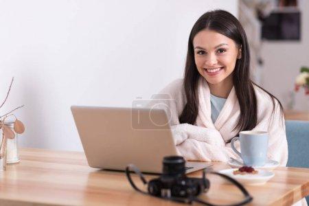 Photo pour Mode de vie agréable. Belle jeune femme détente de charme et buvant un café tout en utilisant son ordinateur portable dans un café. - image libre de droit