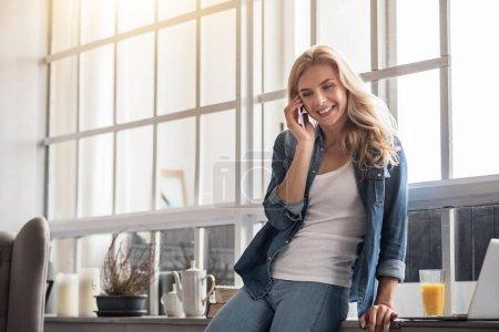 Blond woman talking per mobile phone near window