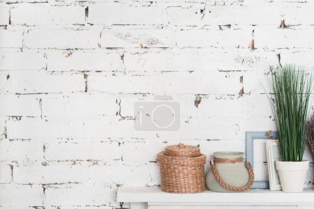 Photo for White on white. Wooden white shelf decorated with flowerpots and picture frames against brick wall. - Royalty Free Image