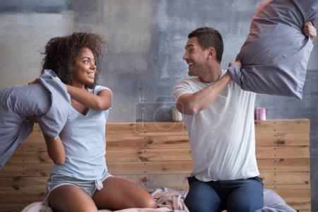 Couple souriant, se battre avec oreillers