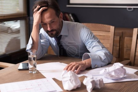 Exhausted cheerless man working long hours