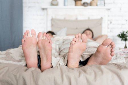 Photo pour Temps de se reposer. Gros plan des pieds séduisante jeune couple gay couché dans son lit tout en dormant et passer le matin au lit. - image libre de droit
