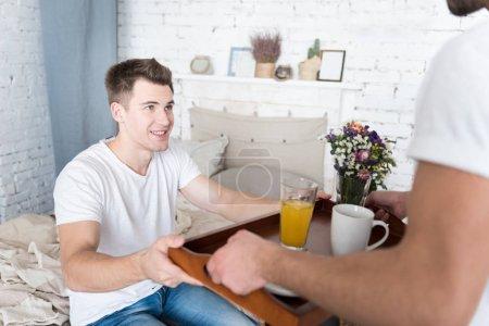 Photo pour Bon appétit. Beau jeune homme heureux recevant des hôtes de son charmant petit ami tenant la barre d'État et de dire Bonjour. - image libre de droit
