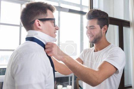 Photo pour Laissez-moi vous aider. Beau jeune homme attachant sa cravate de copains tout en passer du temps ensemble et de profiter de la journée. - image libre de droit