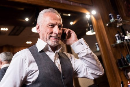 Low angle of businessman having mobile conversation
