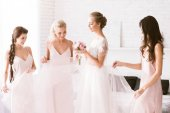 Amused bridesmaids touching the dress of the bride