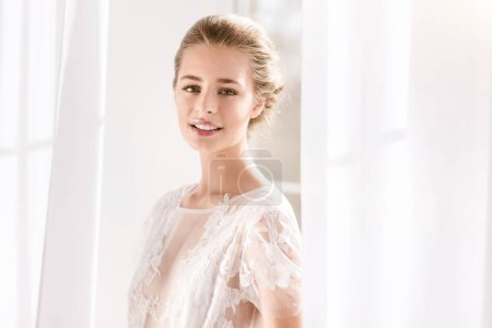 Charming bride standing it the white colored room