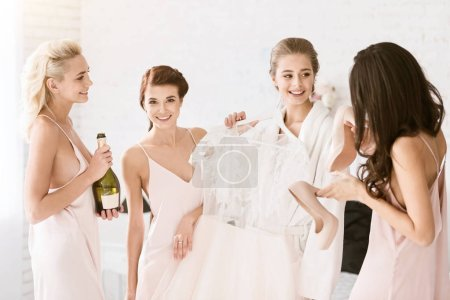 Cheerful bridesmaids helping the bride to get ready for wedding
