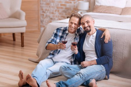 Smiling homosexual couple drinking wine in the bedroom