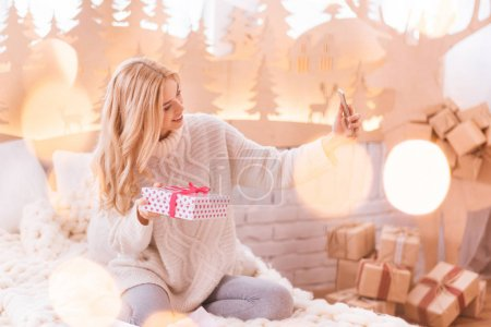 Woman taking a selfie with her present