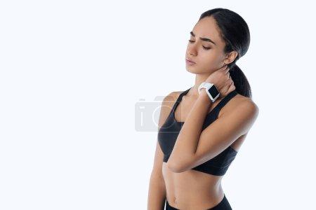 Upset young sportswoman having pain in neck