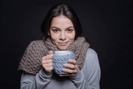 Delighted pleasant woman holding a cup of tea