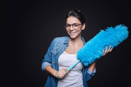 Smiling young housewife holding the dusting brush