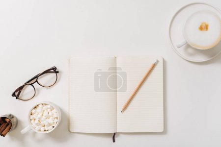 Top view of a pencil lying on the open notebook
