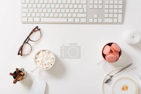Photo for Workplace of a freelancer. Flat lay of a computer keyboard lying on the white desk being surrounded different objects - Royalty Free Image