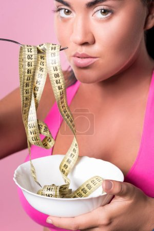 Close up of woman eating measuring tape from plate