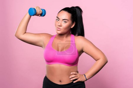 Pretty mulatto woman doing exercises with dumbbell