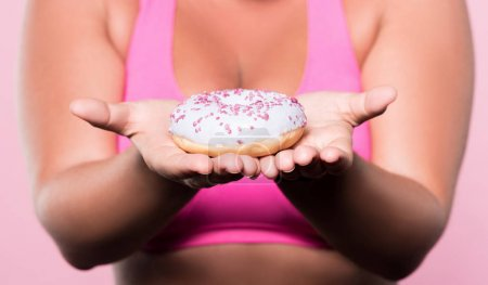 Close up of plump woman holding tasty donut